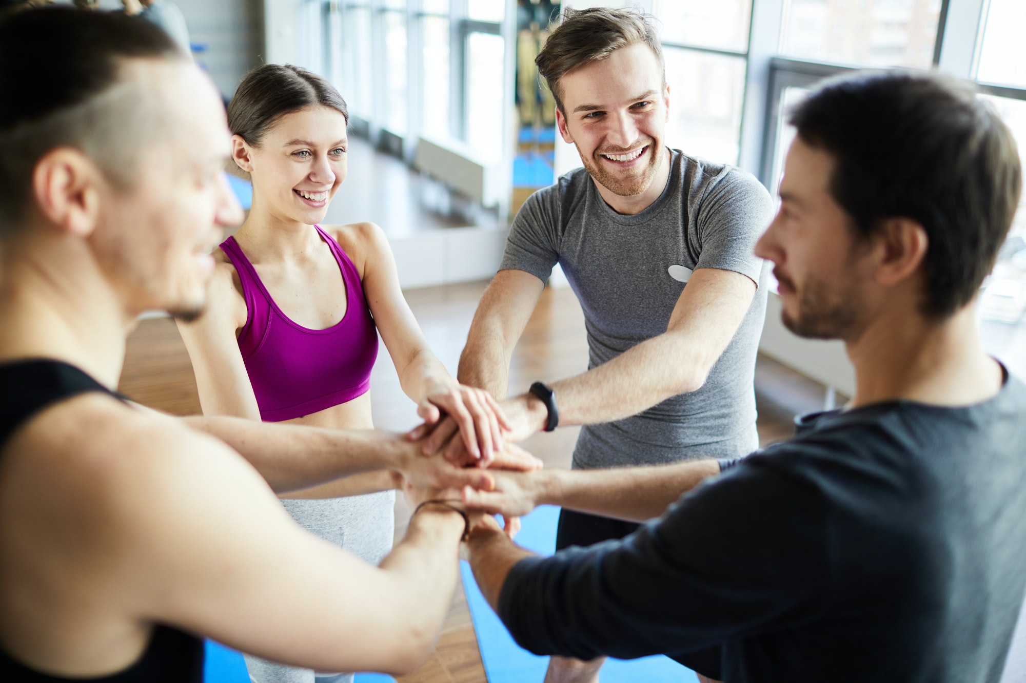 Fitness trainers stacking hands together