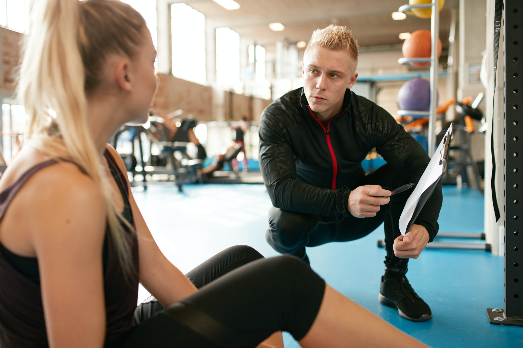 Fitness woman in a gym with personal trainer