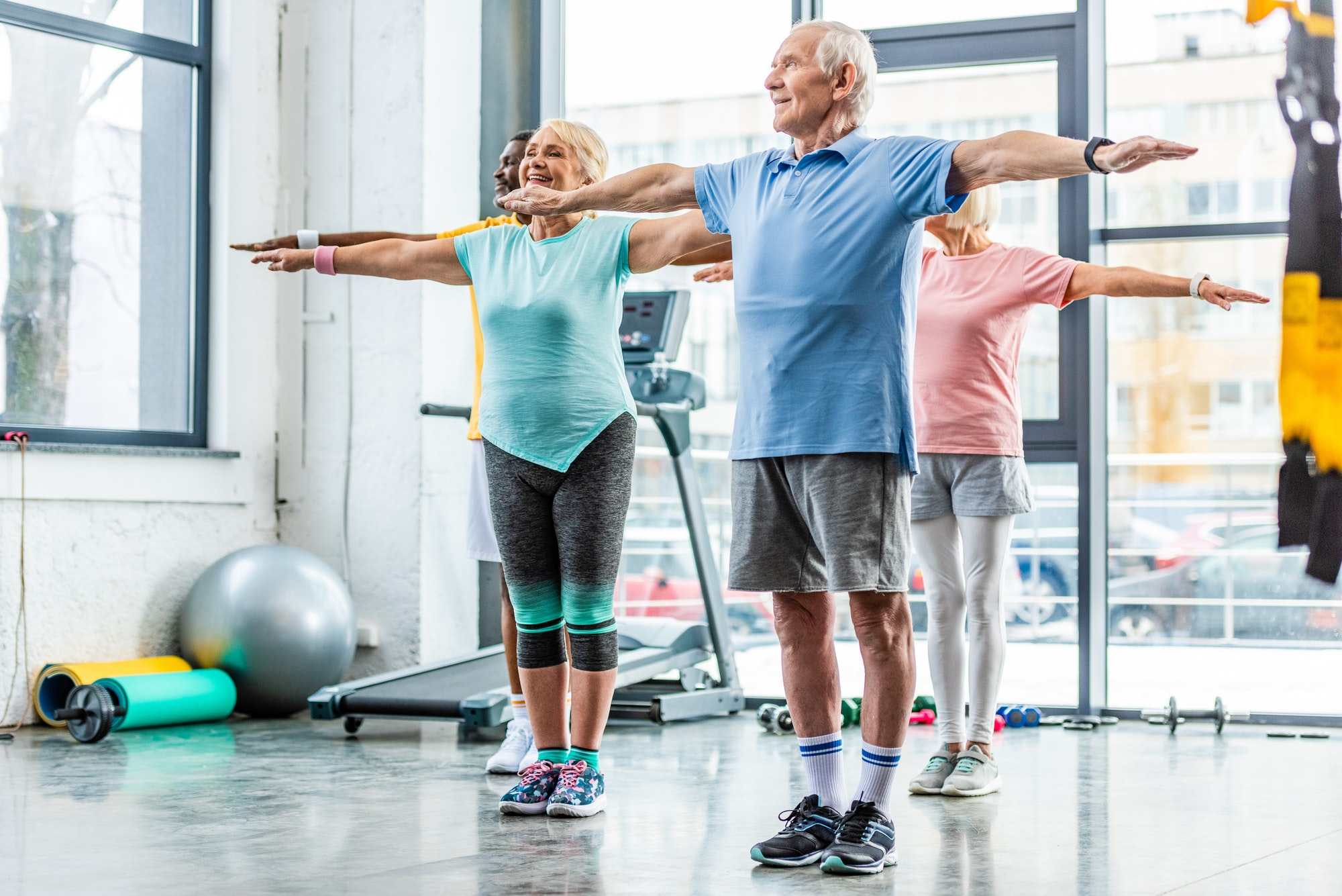 multiethnic senior athletes synchronous doing exercise at sports hall
